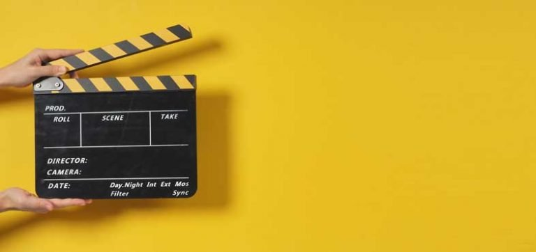 A hand is holding a clapper board or movie slate.It is used in the video production and film industry.